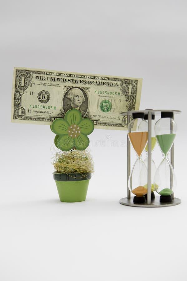 Dinero, planta, reloj de arena en el fondo blanco fotos de archivo