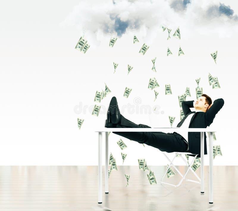 Dinero que cae del concepto del cielo con el hombre de negocios que se sienta en a fotografía de archivo libre de regalías