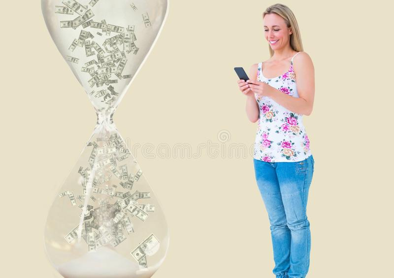 dinero que manda un SMS Mujer con el teléfono, reloj de arena con el dinero cerca fotografía de archivo libre de regalías