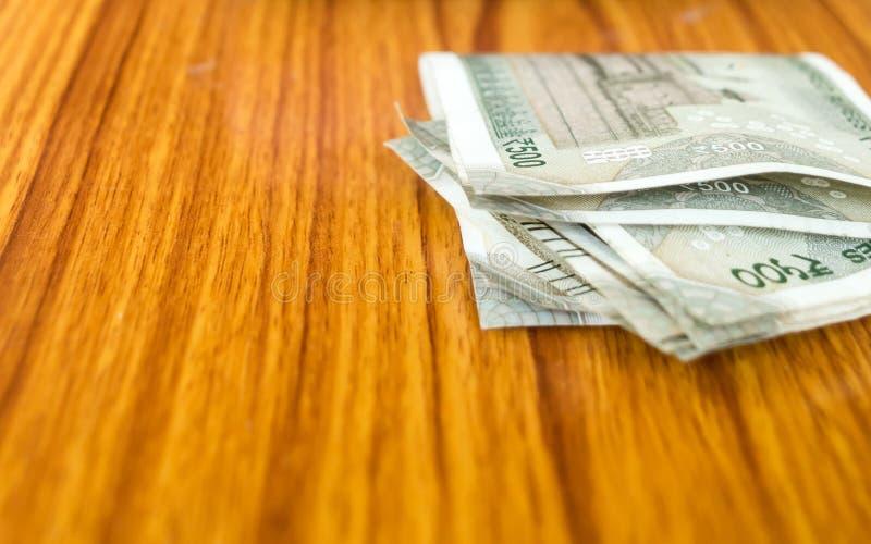 Dinero robado que pone en la tabla Una cierta nota de la rupia de quinientos la India sobre fondo de madera Corrupción en ventajo fotos de archivo libres de regalías