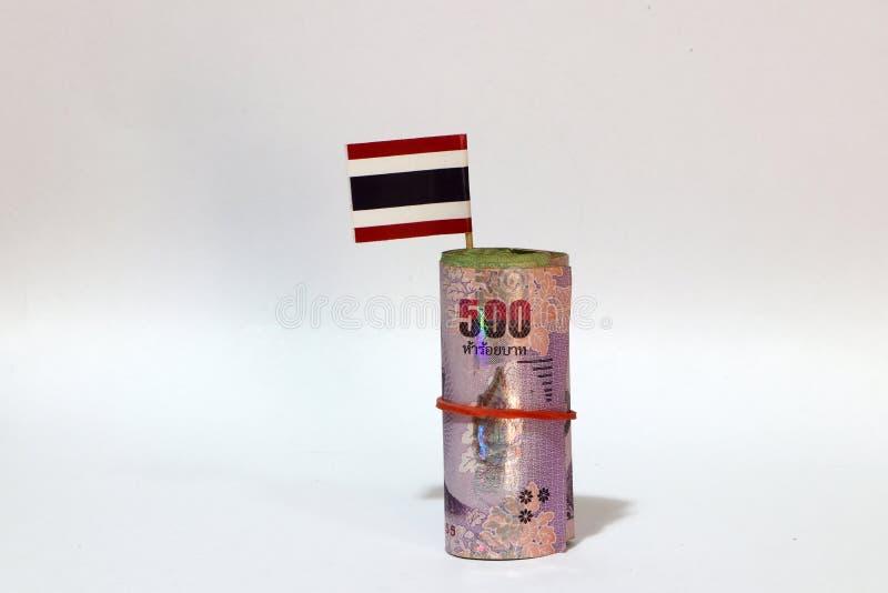 Dinero rodado del billete de banco cinco centenares del baht tailandés y palillo con la mini bandera de Tailandia en el fondo bla foto de archivo