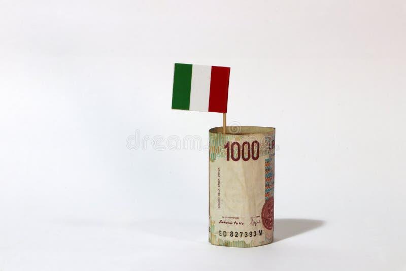 Dinero rodado del billete de banco mil liras de Italia y palillo con la mini bandera de la nación de Italia en el fondo blanco imagen de archivo