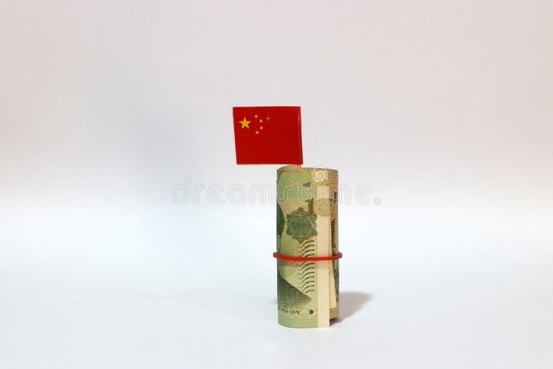 Dinero rodado uno Yuan China del billete de banco y palillo con la mini bandera china en el fondo blanco foto de archivo libre de regalías