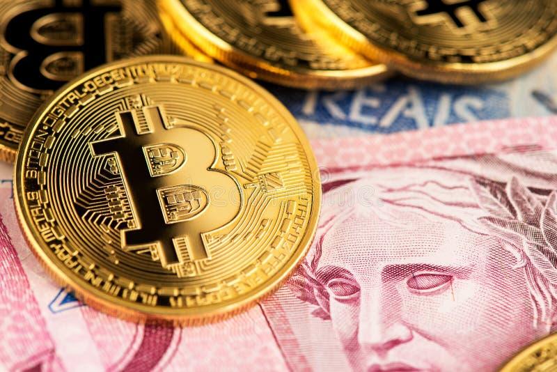 Dinero virtual del cryptocurrency de Bitcoin en billetes de banco reales brasileños del dinero imagen de archivo
