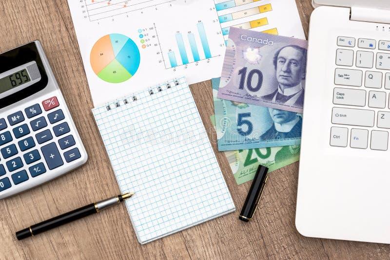 Dinero y calculadora del cuaderno del dólar canadiense fotografía de archivo