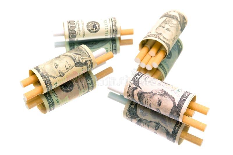 Dinero y cigarrillos en el fondo blanco imagenes de archivo
