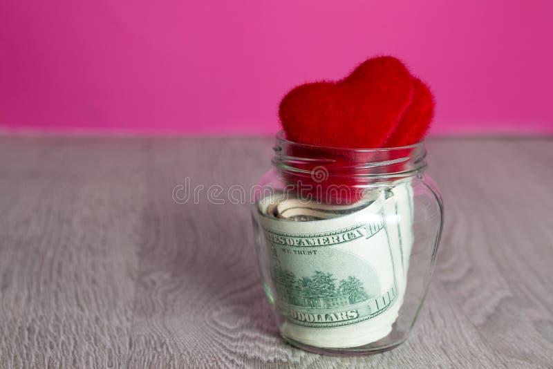 Dinero y corazones rojos Dólares en tarro abierto en fondo de madera gris Copie el espacio Amor Día de tarjeta del día de San Val fotos de archivo libres de regalías