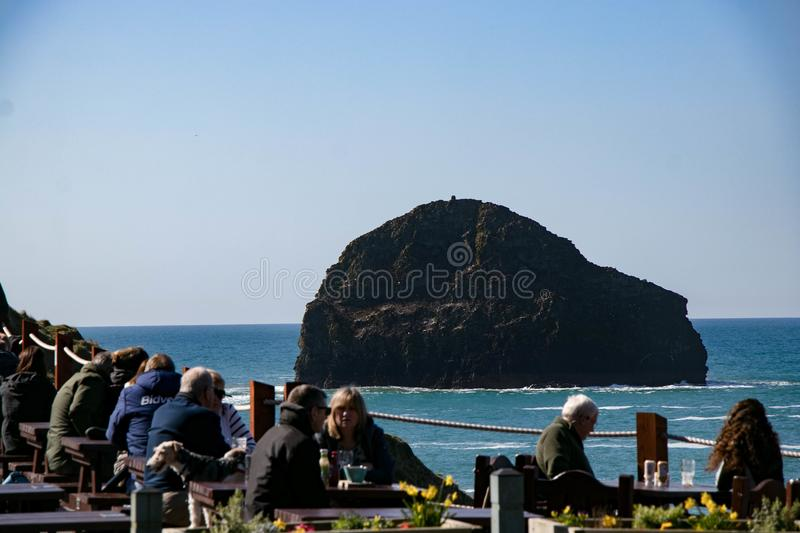 Diners enjoying lunch at an ocean view restaurant at Trebarwith Stand in Cornwall, England stock photography