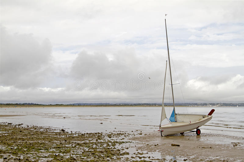 Dinghy on Beach. Small dinghy on deserted beach at low tide on overcast day royalty free stock photos