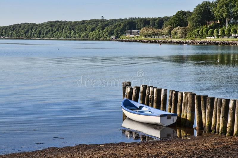 Dinghy at the Coast. Blue and white dinghy at the coast on a summer day stock photography