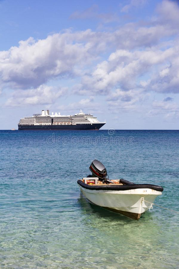 Dinghy and cruise ship. Dinghy with outboard motor and cruise ship, Dravuni Island, Fiji, South Pacific royalty free stock photo