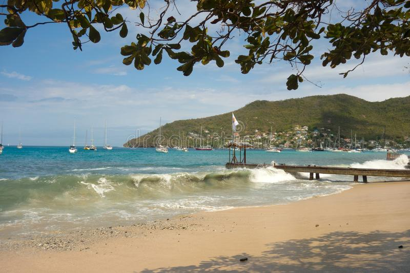 Unseasonal waves crashing against the shore in admiralty bay, bequia. A dinghy dock being being pounded and yachts rocking due to a freak surge in the windward stock photo