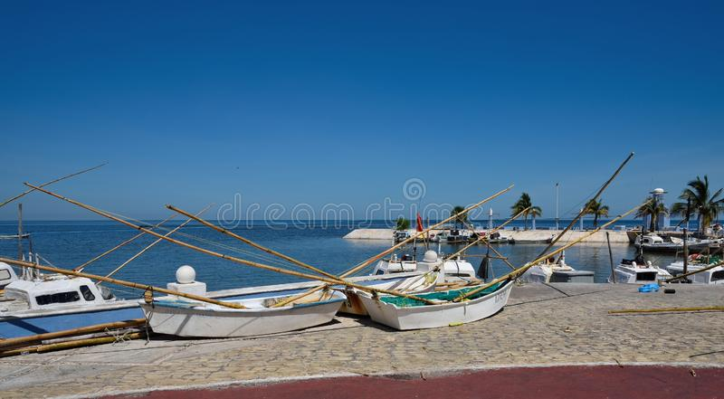 Fishing dinghy. Dinghy with fixed big bamboo poles used for fishing in the golf of Mexico. Boats are in the small fishing haven in Campeche sity. Caribbean sea stock photo