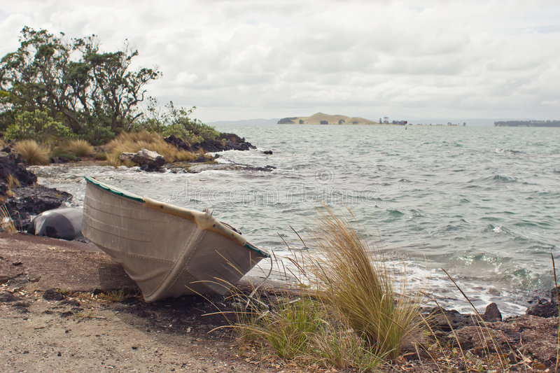 Dinghy on Rangitoto Island. A dinghy rests on the shore of Rangitoto Island in the Hauraki Gulf of New Zealand. Browns Island is in the distance royalty free stock photography
