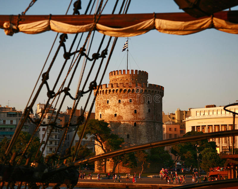 Dinghy at the sunset. The View at Thessaloniki from the excursion boat along the Aegean Sea. The White Tower in Thessaloniki is an architectural monument and a stock image