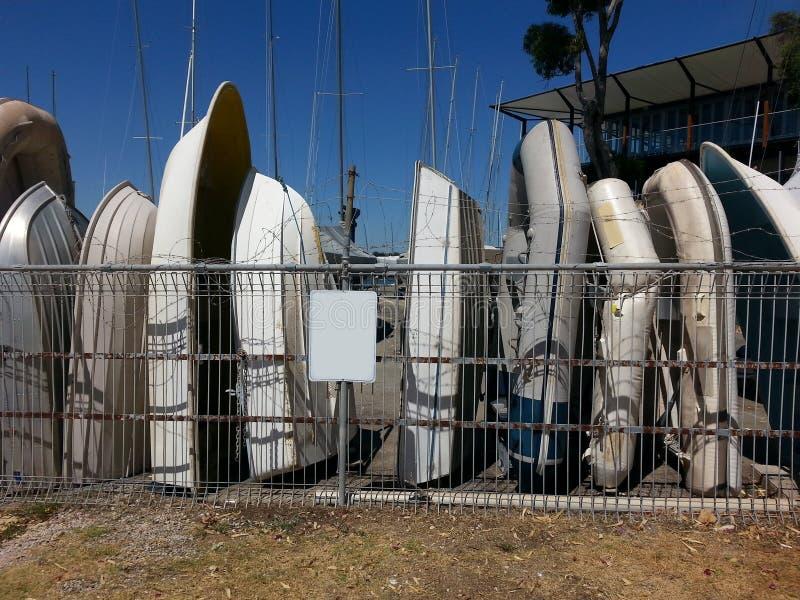 Dingies velhos dos barcos no armazenamento atrás da cerca de fio descoberta fotografia de stock royalty free