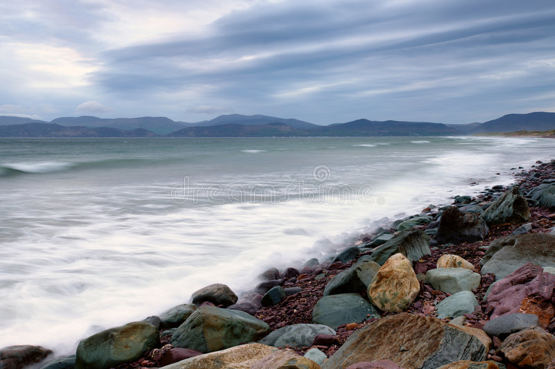 Dingle Bay. Incoming tide washes over rocks and sand at Rossbeigh Strand in Dingle Bay, Co.Kerry, Republic Of Ireland stock photos