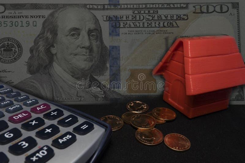 Dinheiro, calculadora, banco de moedas com modelo vermelho da casa na tabela imagem de stock royalty free