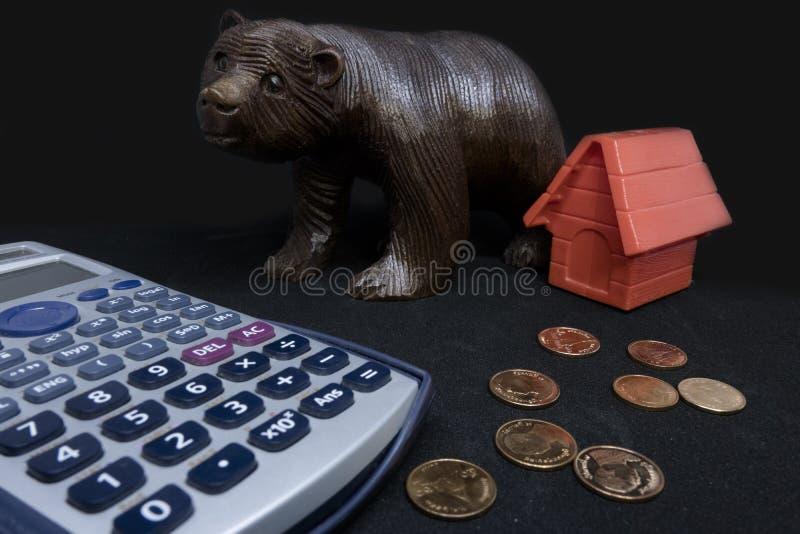 Dinheiro, calculadora, banco de moedas com modelo vermelho da casa na tabela fotografia de stock royalty free