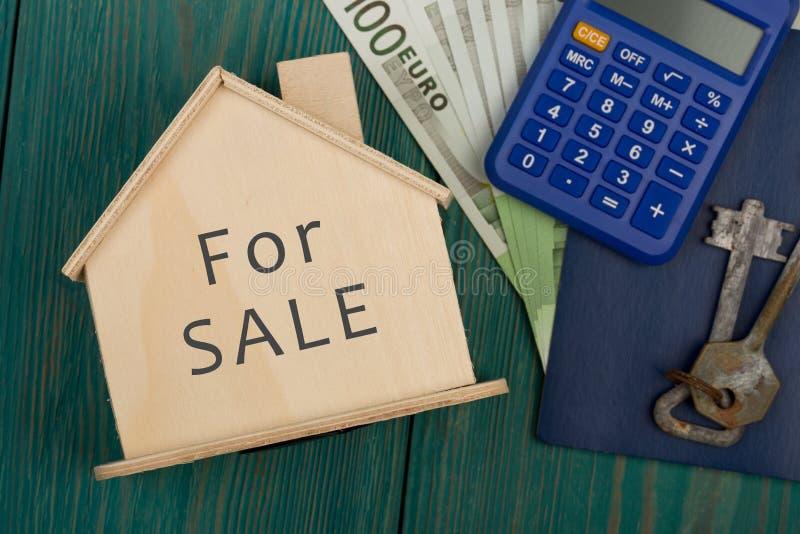 dinheiro, calculadora, pouca casa com texto & x22; Para SALE& x22; no azul imagens de stock