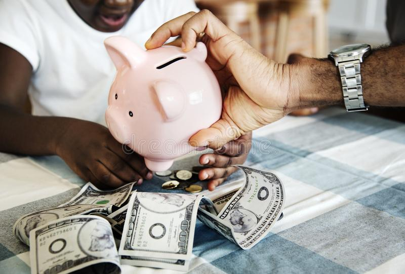 Dinheiro da economia do paizinho e da filha ao mealheiro foto de stock royalty free