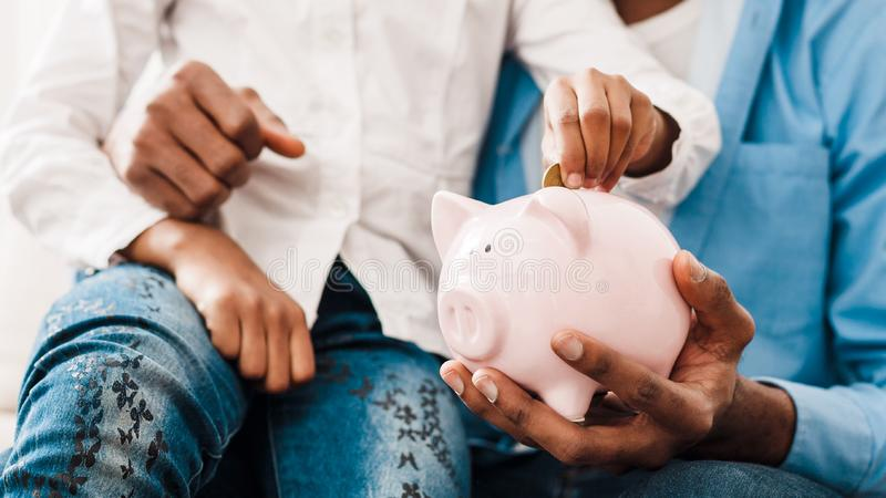Dinheiro da economia do paizinho e da filha ao mealheiro imagens de stock