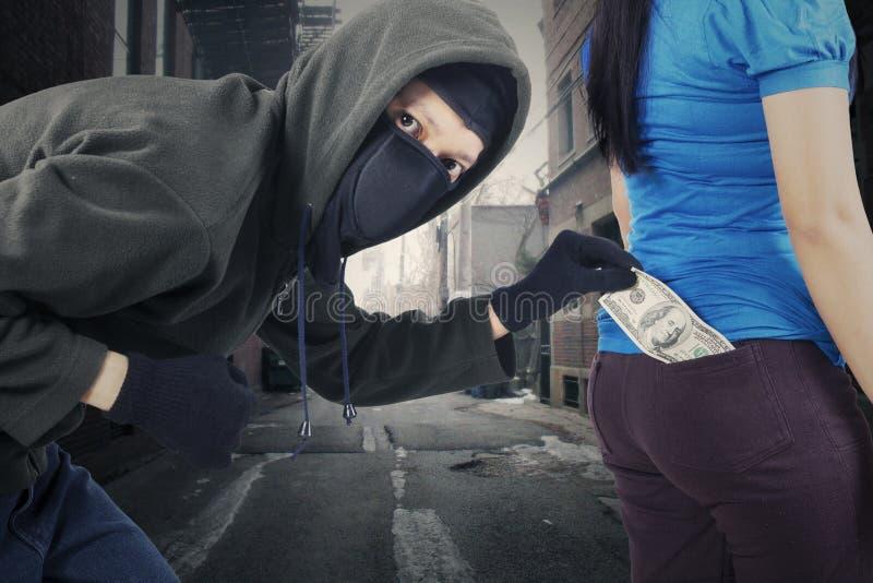 Dinheiro da estola do assaltante na rua fotografia de stock royalty free