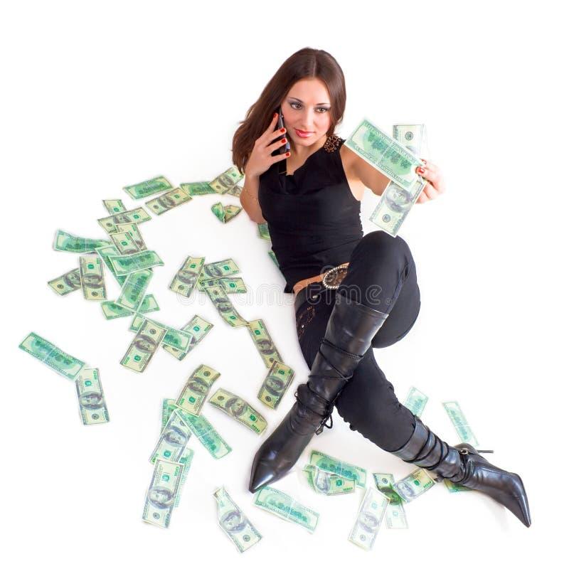 Dinheiro da terra arrendada da menina e chamada pela pilha fotografia de stock royalty free