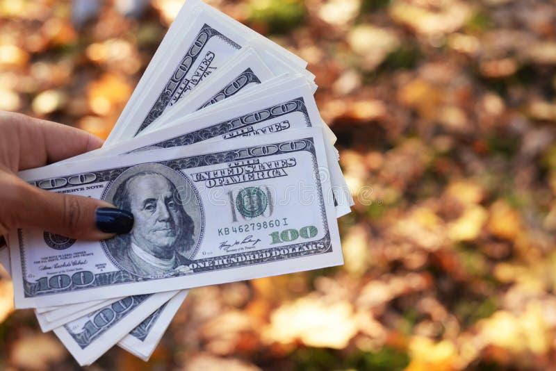 Dinheiro das cédulas cem dólares na mão de uma menina fotos de stock