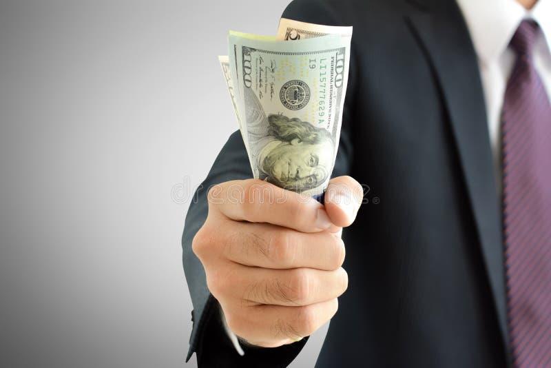 Dinheiro de agarramento da mão do homem de negócios, cédulas do dólar americano (USD) fotos de stock royalty free