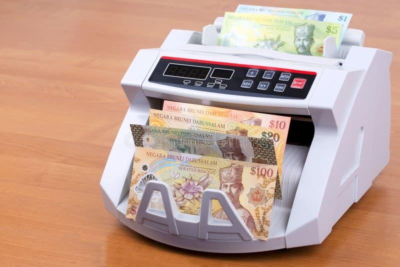 Dinheiro de Brunei Darussalam em uma máquina de contagem imagens de stock royalty free