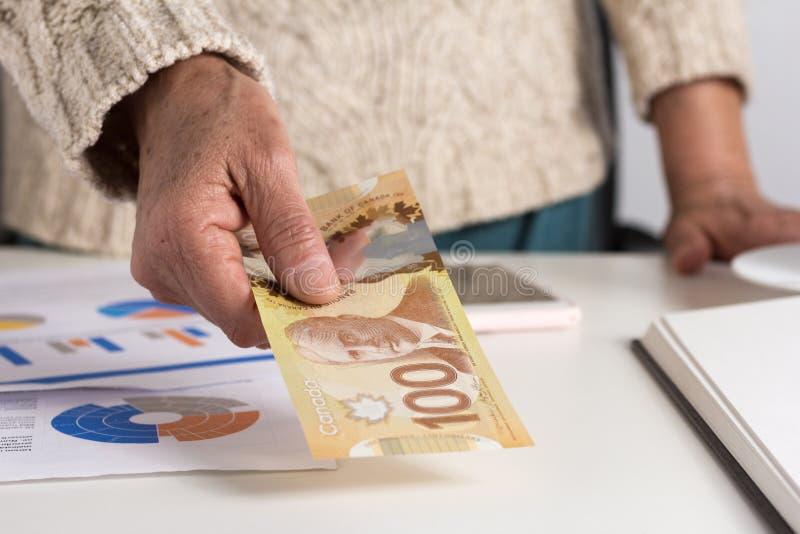 Dinheiro de Canadá: Dólares canadenses Pessoa que dá papernotes sobre foto de stock royalty free
