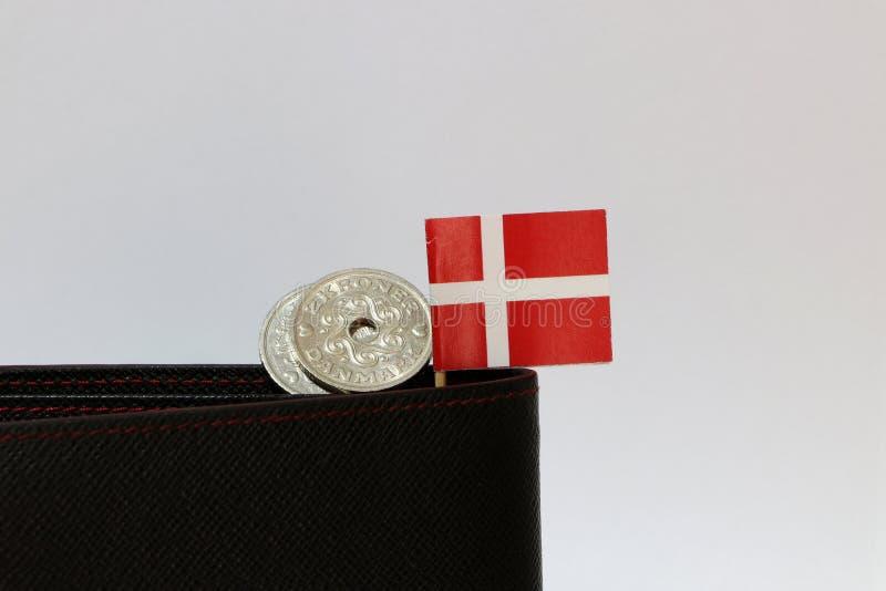 Dinheiro de duas coroas dinamarquesas das moedas e mini vara da bandeira de Dinamarca na carteira preta com fundo branco fotos de stock