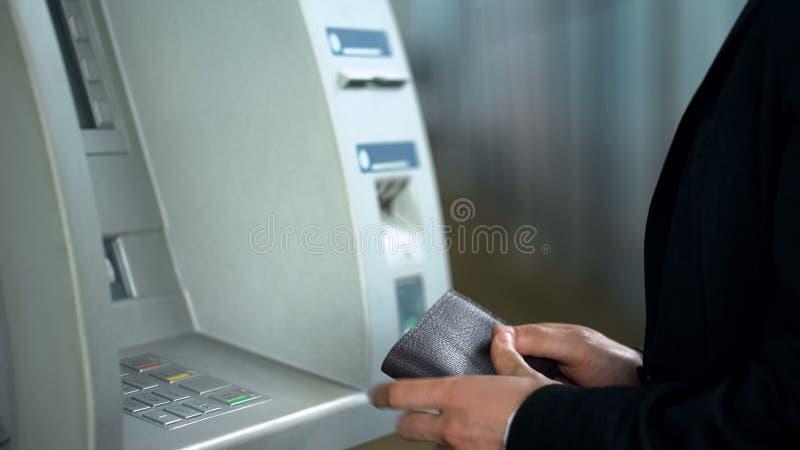 Dinheiro de espera do homem de negócios do ATM após ter introduzido o cartão e ter dado entrada ao código do pino foto de stock