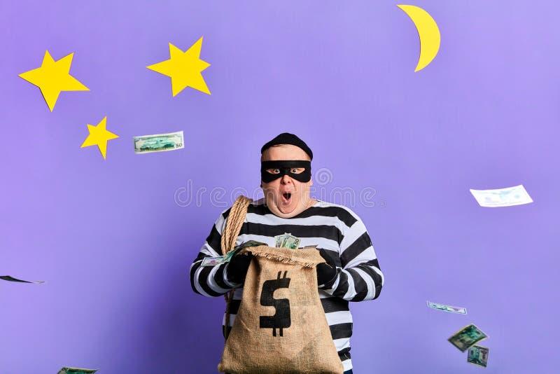 Dinheiro de jogo do prisioneiro gordo impressionante entusiasmado fotografia de stock