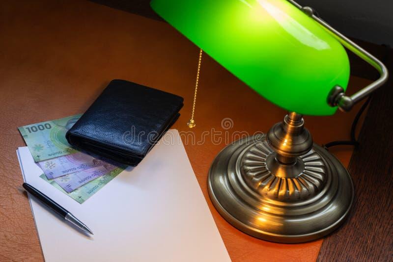 Dinheiro do Chile, pesos, em uma mesa à moda leve com uma lâmpada bancária fotos de stock