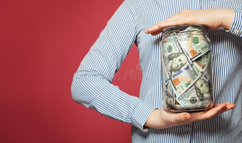 Dinheiro do dinheiro dólares americanos no frasco no fundo vívido imagens de stock