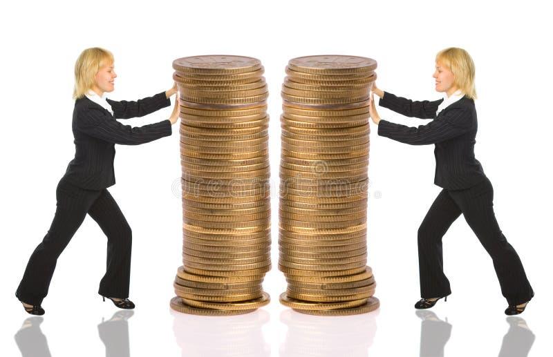 Dinheiro do rouleau do impulso de duas mulheres de negócios foto de stock royalty free