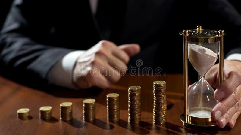 Dinheiro do salário do empresário bem sucedido no projeto de investimento lucrativo, sandglass que medem o tempo imagens de stock royalty free