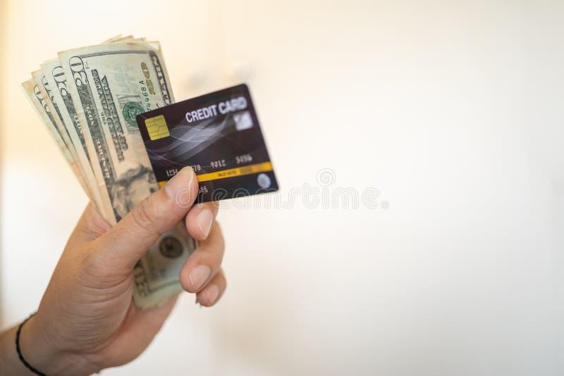 Dinheiro e conceito do neg?cio Feche acima da mão do homem que guarda o cartão de crédito e a cédula de 20 dólares americanos com fotos de stock royalty free