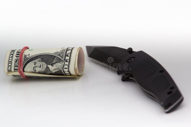 Dinheiro e faca no fundo branco foto de stock royalty free