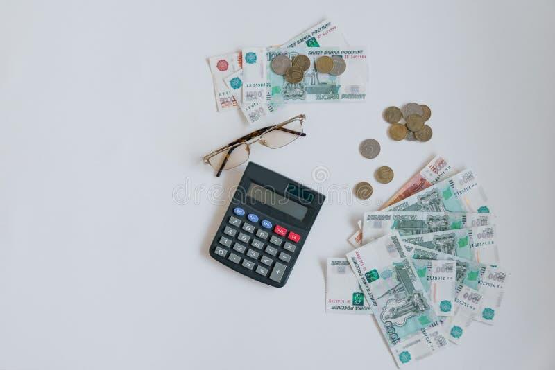 Dinheiro em Rússia Cédulas cinco e mil rublos, fundo, foco seletivo, na tabela, nos vidros e no a fotografia de stock