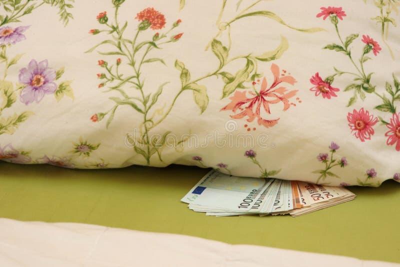 Dinheiro escondido na cama sob o descanso fotos de stock royalty free