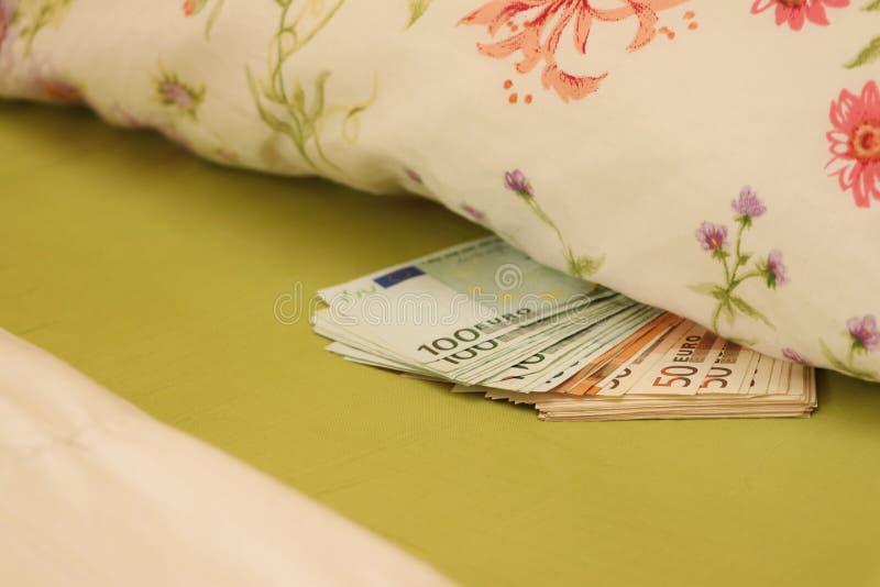 Dinheiro escondido na cama sob o descanso imagens de stock royalty free