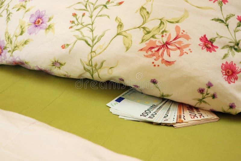 Dinheiro escondido na cama sob o descanso foto de stock
