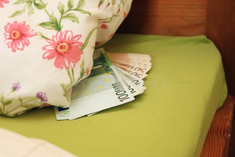 Dinheiro escondido na cama sob o descanso fotos de stock