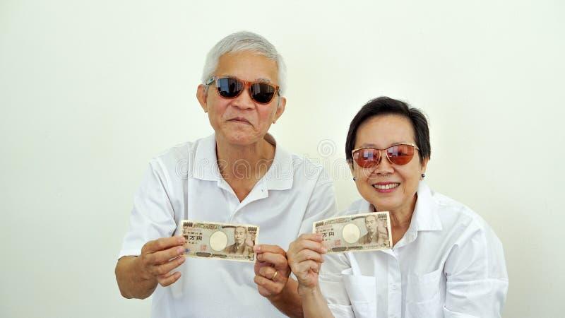 Dinheiro guardando rico feliz do iene japonês dos pares asiáticos do eldery dentro foto de stock royalty free