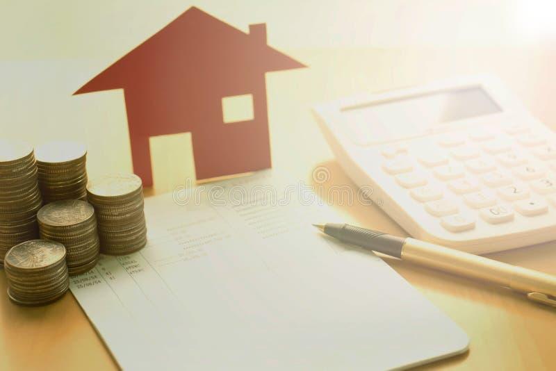 Dinheiro, moeda da pilha com livro de economia e casa do papel, conceito foto de stock