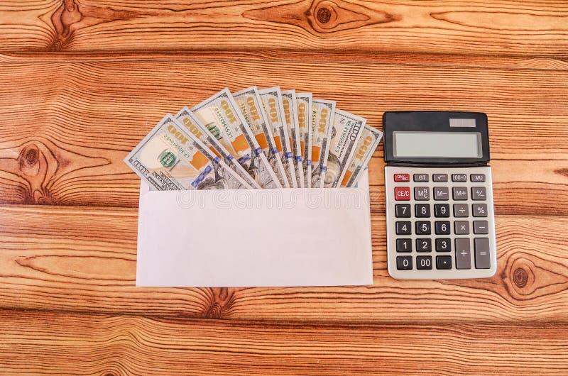 Dinheiro nas denominações de 100 dólares em um envelope branco e em uma calculadora em uma tabela de madeira Vista de acima imagem de stock royalty free
