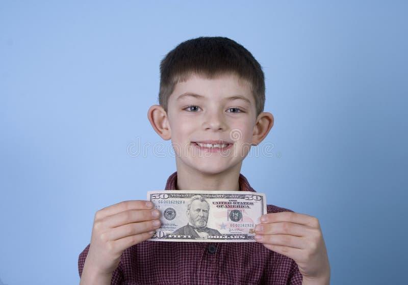 Dinheiro novo e sorriso da terra arrendada do menino fotografia de stock royalty free